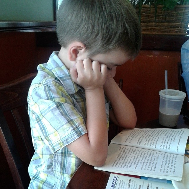 Out to eat for lunch on daddy's Friday off. This boy is reading another Pokemon book :-)